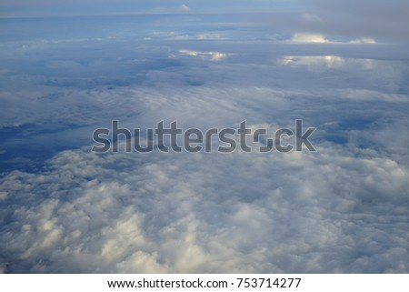 View of beautiful abstract soft white cloud with shades of blue sky background from above flying plane window in bright morning sunrise #753714277