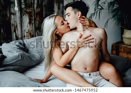 View of beautiful brunet macho and gorgeous blonde woman, almost naked, sit in bed on bedclothes, embracing, sensual, intense, tender, white loft room #1467475952