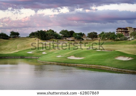 View of beautiful golf course at sunset with lake in foreground in Scottsdale, Arizona