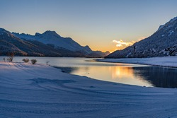 View of beautiful sunet at Lake Silvaplana, Switzerland, in cold winter evening with foreground snow and mountain range background