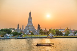 View of beautiful Temple of Dawn or Wat Arun and boats on Chao Phraya River at sunset with shining sun. Bangkok, Thailand