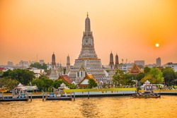 View of beautiful Temple of Dawn or Wat Arun and Thonburi west bank of Chao Phraya River at sunset with shining sun. Bangkok, Thailand