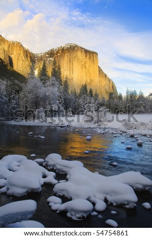 View of beautiful Yosemite valley in winter with the Merced river and snow covered El Capitan at sunset