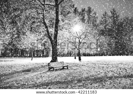 View of bench and shining lantern through snowing. Black and white. Night shot.