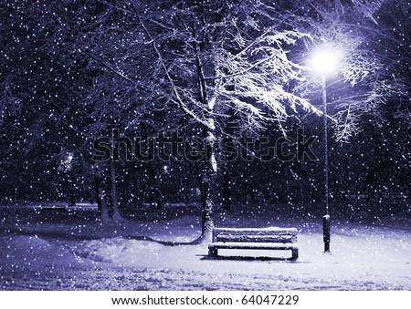 View of bench and shining lantern through snowing. Blue tone. Night shot.