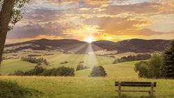 View of bench, valley, mountains, hills and sunset.