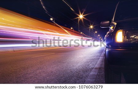 View of black SUV car parking on the  road with  traffic light trails ,long shutter speed exposure. #1076063279