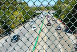 View of blurry highway traffic seen through chain link fence from overpass.