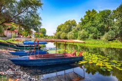 View of  Boats with a thatched roofs on the pier. Skadar lake tour. Location:  Skadar Lake National Park, Montenegro, Balkans, Europe.