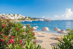 View of Bodrum Beach, Aegean sea, traditional white houses, flowers, marina, sailing boats, yachts in Bodrum town Turkey.