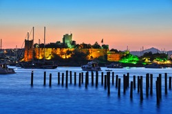 View of Bodrum harbor and Castle of St. Peter after sunset. Turkish Riviera.