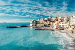 View of Bogliasco. Bogliasco is a ancient fishing village in Italy, Genoa, Liguria. Mediterranean Sea, sandy beach and architecture of Bogliasco town. Cloudy blue sky sunny day idyllic scenery, winter