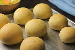 View of bread buns for make Korean Garlic Cheese Bread one of popular street food, made from bun, filling with cheese and topping with butter,garlic and herb. Dark wooden background.