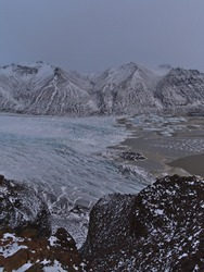 View of break-off edge of Skaftafellsjökull, an outlet glacier of Vatnajökull, in Skaftafell national park in south Iceland with glacier lake and rough snow-covered mountains in winter season.