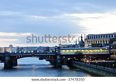 View of bridge and cityscape on Thames river in London at night