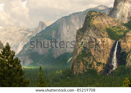 view of Bridleveil falls and half dome with clouds creating a patchwork of light dancing across  Yosemite national Park, California - stock photo