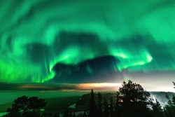View of brilliant green Aurora shining over Swedish foggy forest landscape in mountains, light rays from a village and Northern Lights color sky in different soft colors, Northern Sweden, Scandinavia