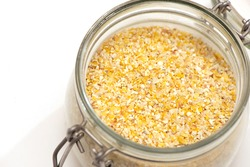 view of broken wheat groats in glass jar close-up