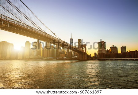 View of Brooklyn Bridge and Manhattan skyline WTC Freedom Tower from Dumbo at sunset, Brooklyn. Brooklyn Bridge is one of the oldest suspension bridges in the USA #607661897