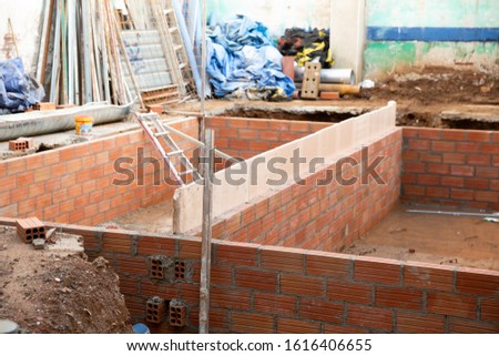 View of building under reconstruction - tools and materials near pit with brick construction