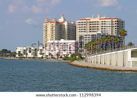 View of buildings on the edge of  Sarasota Bay, Sarasota, Florida from the water with palm trees, blue sky and clouds.
