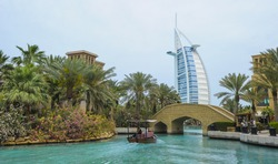 View of Burj Al Arab (Tower of the Arabs) hotel from Madinat Jumeirah hotel, Dubai. Madinat is a luxury resort which includes hotels and souk spreding across over 40 hectars.