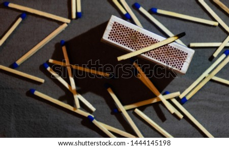 View of burned match on top of the matchbox, with blue unburned matches  laying around the box in the background. With a visible shade.