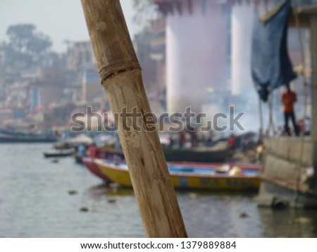 View of burning Ghat with bamboo pole in foreground #1379889884