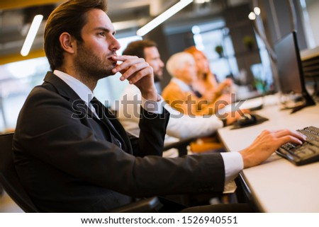 View of businessman executive in group meeting with other businessmen and businesswomen in modern office with computer