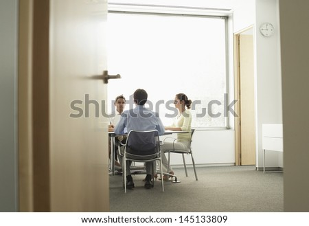 View of businessmen and businesswoman having a meeting in boardroom though doorway