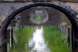 View of canal in Amsterdam, Looking through under bridge, Amsterdam canal cruises is very famous activities, Tourist attraction, Netherlands.