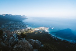 View of Cape Town from the top of Table Mountain as the sun is setting. Views of all of Cape Town with the cable cars and rocky landscape of the seaside town. Bantry Bay, lions head, Camps bay, City.