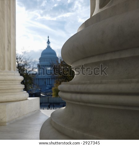 View of Capitol building in distance from behind columns of the Supreme Court building in Washington D.C.