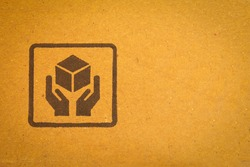 View of cardboard with handle with care sign. Package box with symbol indicating fragile items and need careful handling.