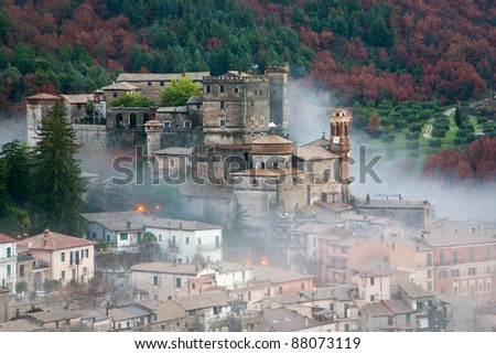 View of Castle of Arsoli and the village surrounded by morning fog with forest in autumnal colors in background