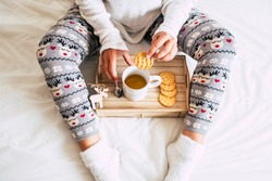 View of caucasian woman at home doing breakfast on the bed in winter season - christmas pants and decorations for lonely people celebrating and eating cookies and coffee