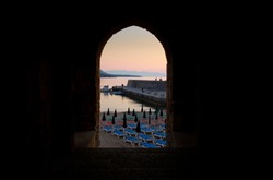 View of Cefalu Harbour wall during sunset through an archway, Cefalu, Sicily, Italy - June 2015