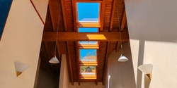 View of ceiling of gable roof without attic with three plastic windows, finished with clapboard,wooden beam,identical suspended white frosted lamps,2 symmetrically on white walls.Selective focus.