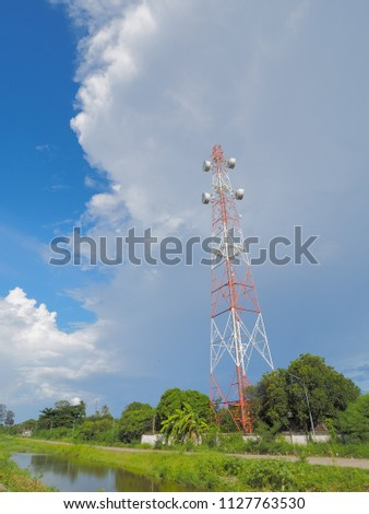 view of Cellular Signal Tower with fat clouds in blue sky background #1127763530