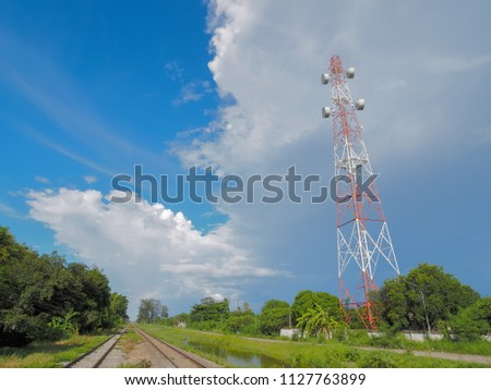 view of Cellular Signal Tower with fat clouds in blue sky background #1127763899