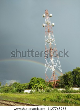 view of Cellular Signal Tower with rainbow in the sky background #1127765966
