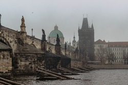 View of Charles bridge, Old Town bridge tower and Vltava River in foggy morning,Prague,Czech Republic.Buildings and landmarks of Old town. Amazing European cityscape.Mystical urban scenery