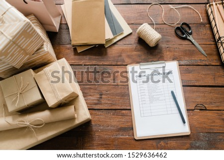 View of checklist paper, pen, packed boxes, threads, scissors and stack of notepads on wooden background