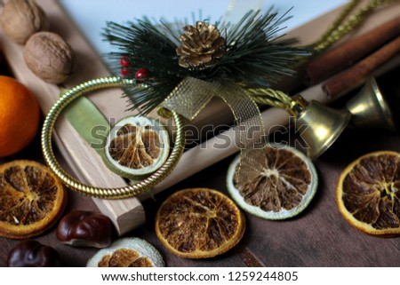 View of Christmas decor. Christmas objects: dried sliced orange, cinnamon, pine cone, fir branch, cup coffee, cheesecake, walnut, golden Christmas bells.