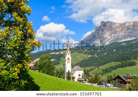 Stock Photo View of church in La Villa village on sunny summer day with mountains in the background, Trentino Alto Adige, Italy