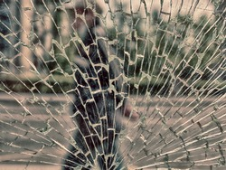 View of city and people through cracked glass. City as habitat with increased danger, mental stress concept (environmental stress, riots, accidents, risky transport, diseases, maniacs, murderers etc.)