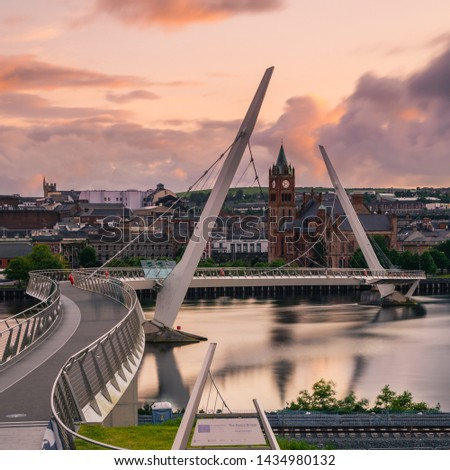 View of city of Derry Northern Ireland with the peace bridge and guildhall with long exposure of the river foyle