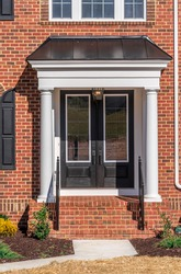 View of classic portico entrance covered w/ dark color metal roof, supported by two colonial white vinyl wrap columns w/ decorative caps and trim black baluster railing on a brick luxury American home