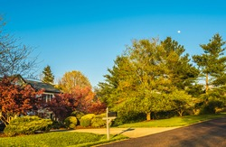 View of clear sky with full moon rising over Midwestern neighborhood early in the evening in spring; well landscaped front yard on the left