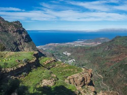 View of cliffs and rocky atlantic coast in the north west of Gran Canaria with view on city of Agaete, serpentine road and green hills. Canary Islands, Spain.